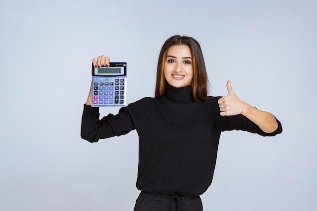 Mulher segurando uma calculadora azul e apreciando o resultado final.