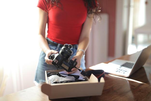 Mulher segurando uma câmera com um caderno em cima da mesa