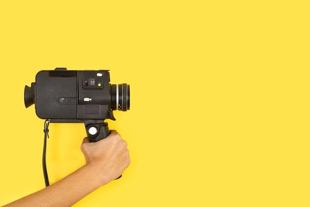 Mulher segurando uma câmera de oito milímetros em um fundo amarelo com espaço de cópia