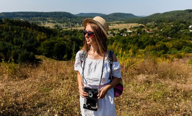 Mulher segurando uma câmera e desviar o olhar
