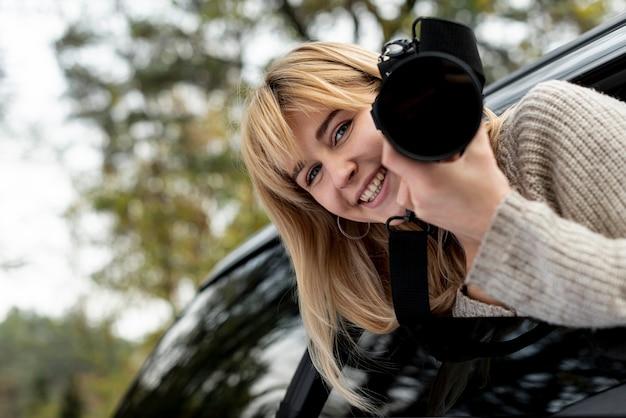 Mulher segurando uma câmera e olhando para o fotógrafo
