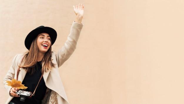 Mulher segurando uma câmera enquanto uma de suas mãos está levantada