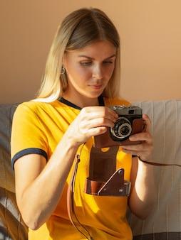 Mulher segurando uma câmera fotográfica retrô
