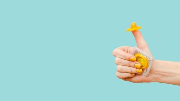 Mulher segurando uma camisinha amarela no dedo