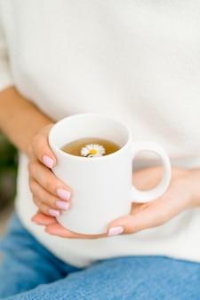 Mulher segurando uma caneca branca com chá