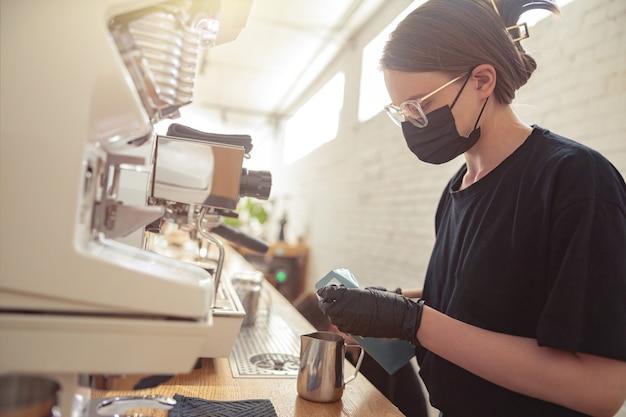 Mulher segurando uma caneca de aço inoxidável e usando a máquina de café
