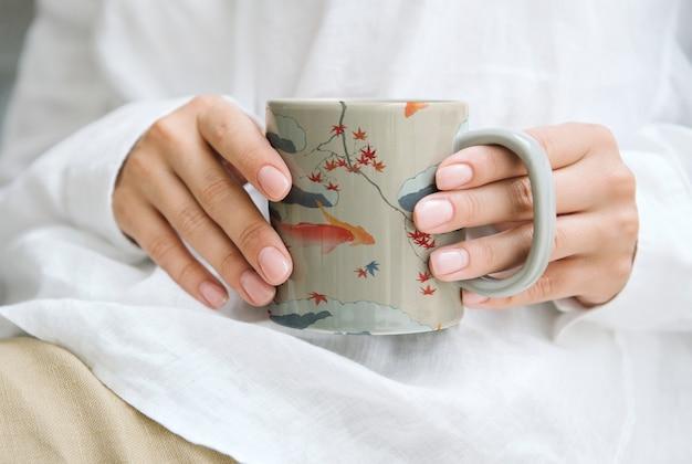 Mulher segurando uma caneca de café com padrão japonês, remix de uma obra de arte de watanabe seitei