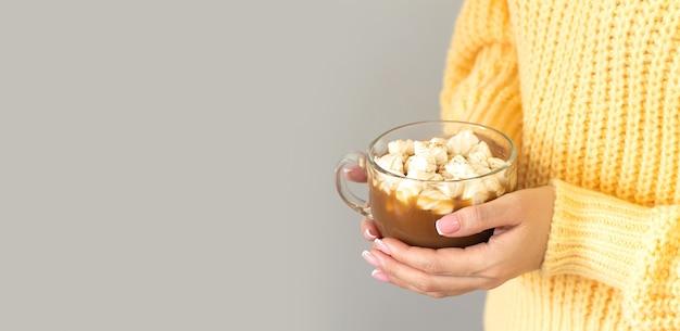 Mulher segurando uma caneca grande de chocolate quente ou chocolate com marshmallow.