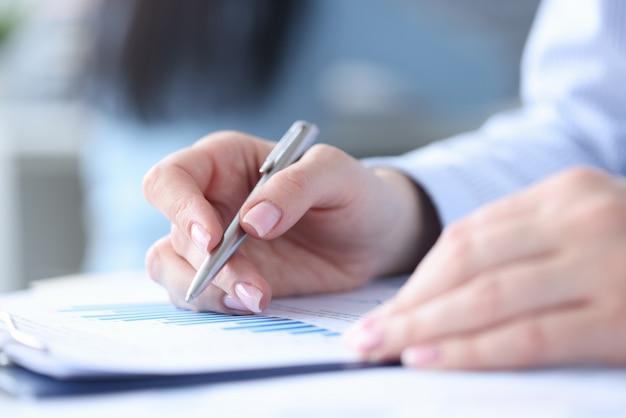 Mulher segurando uma caneta nas mãos e estudando gráficos em documentos close-up