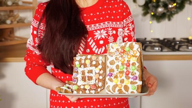 Mulher segurando uma casa de pão de mel contra as decorações de natal Foto Premium
