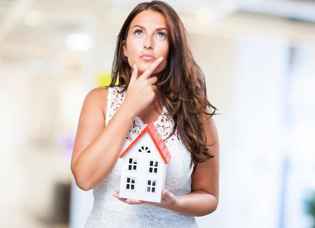 Mulher segurando uma casa e pensar em algo