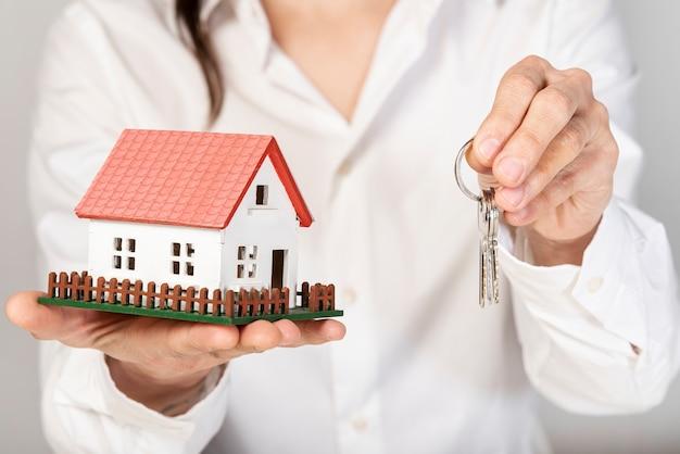 Mulher segurando uma casa modelo de brinquedo e chaves