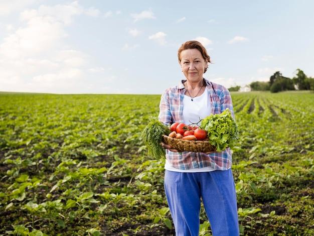 Mulher segurando uma cesta cheia de legumes com espaço de cópia