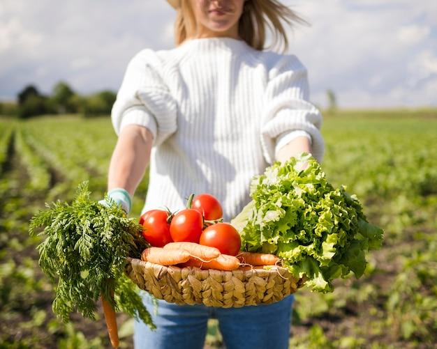 Mulher segurando uma cesta cheia de legumes na frente dela