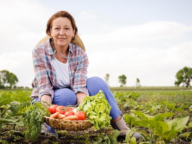 Mulher segurando uma cesta cheia de legumes