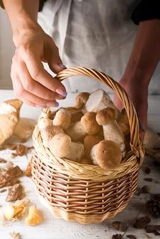 Mulher segurando uma cesta com cogumelos