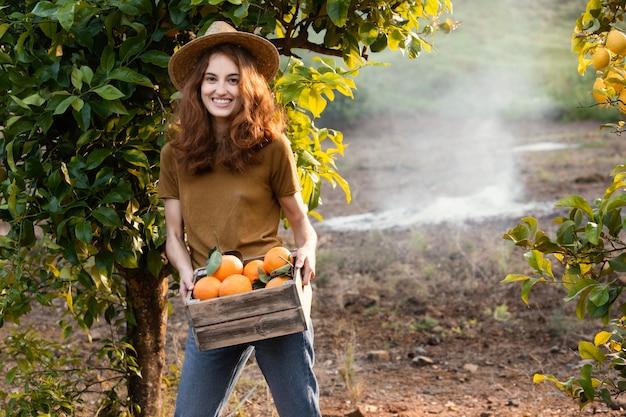 Mulher segurando uma cesta com laranjas