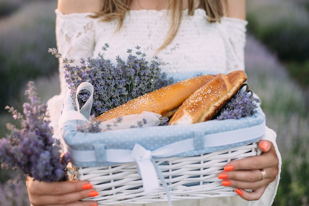 Mulher segurando uma cesta com pão e lavanda