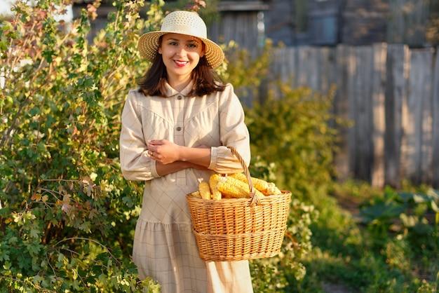 Mulher segurando uma cesta com uma colheita de milho na mão.