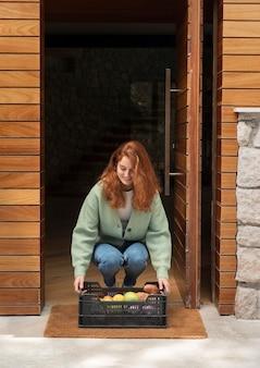 Mulher segurando uma cesta de alimentos que foi entregue em sua porta