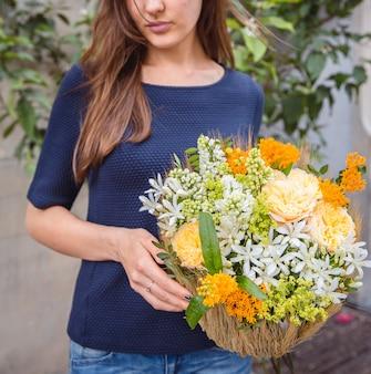 Mulher segurando uma cesta de flores amarelas e brancas.