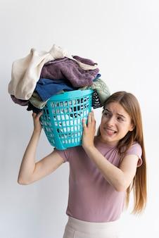 Mulher segurando uma cesta de roupas no ombro