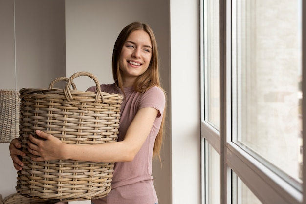 Mulher segurando uma cesta enquanto olha pela janela