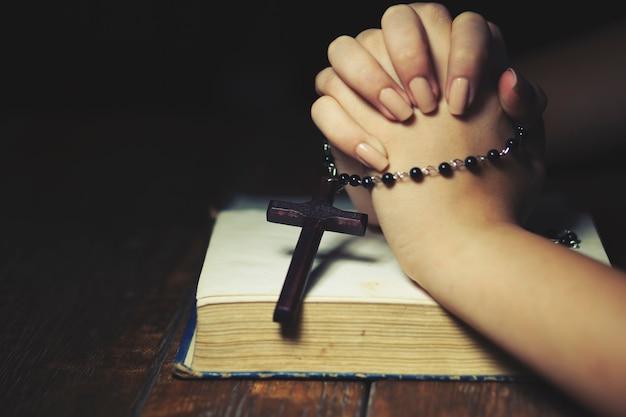 Mulher segurando uma cruz enquanto reza