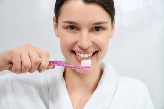 Mulher segurando uma escova de dente rosa com pasta de dente no banheiro