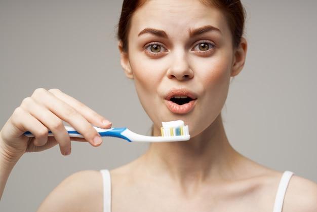 Mulher segurando uma escova de dentes com pasta nas mãos, higiene odontológica