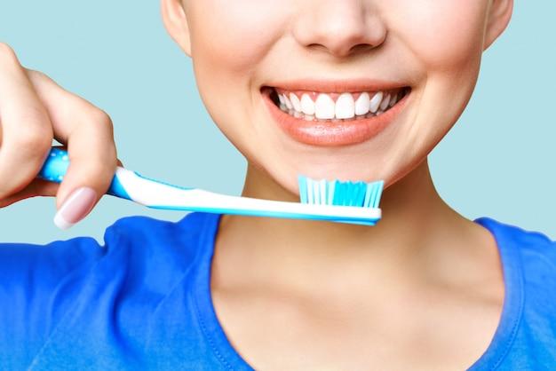 Mulher segurando uma escova de dentes na mão e sorrindo