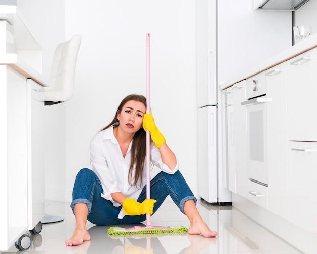Mulher segurando uma esfregona e sentada no chão