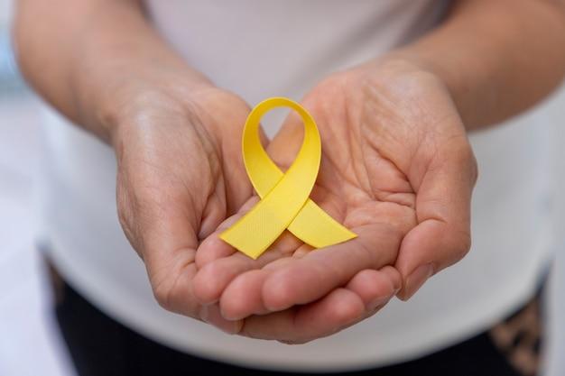 Mulher segurando uma fita amarela nas palmas das mãos. campanha de prevenção do suicídio. amarelo de setembro.