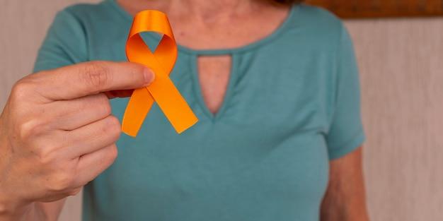Mulher segurando uma fita laranja para aumentar a conscientização sobre a leucemia