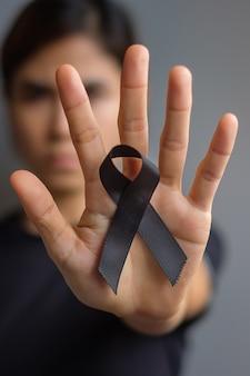 Mulher segurando uma fita preta para melanoma e câncer de pele, mês de conscientização sobre lesões por vacina, tristeza e descanso em paz. conceito de saúde e racismo