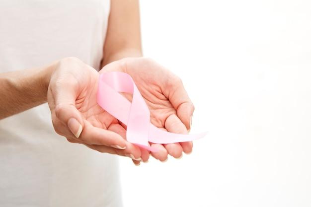 Mulher segurando uma fita rosa.