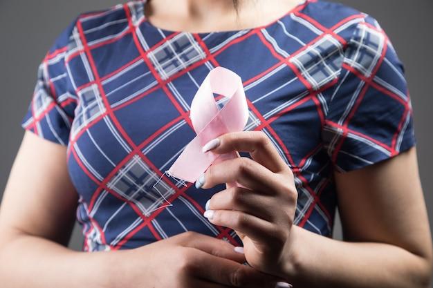 Mulher segurando uma fita rosa