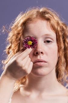 Mulher segurando uma flor sobre o olho dela