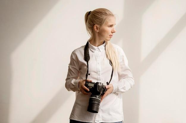 Mulher segurando uma foto de câmera, olhando para longe