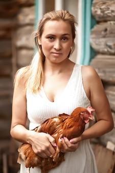 Mulher segurando uma galinha em um galinheiro. animais de fazenda.