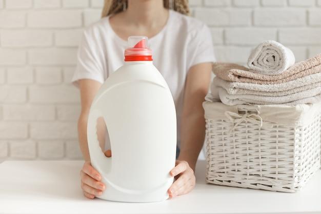 Mulher segurando uma garrafa branca com detergente