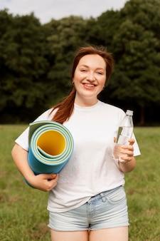 Mulher segurando uma garrafa de água e um tapete de ioga ao ar livre