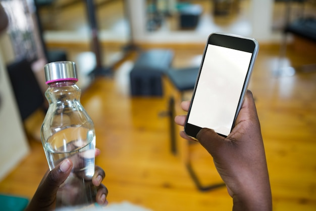 Mulher segurando uma garrafa de água e usando o celular