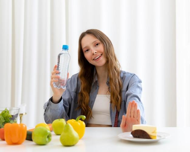 Mulher segurando uma garrafa de água