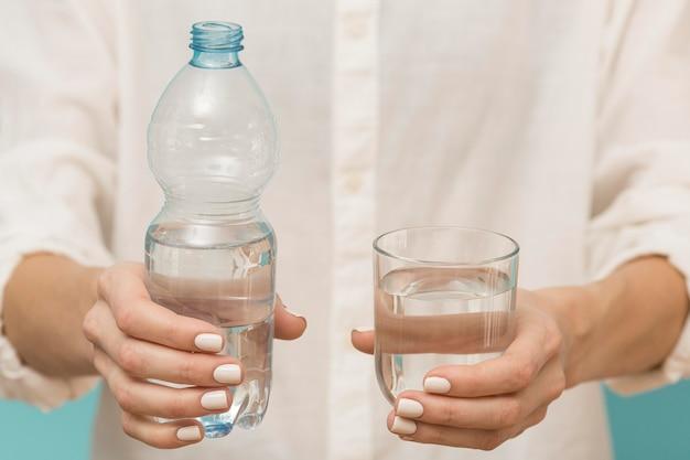 Mulher segurando uma garrafa de plástico e um copo