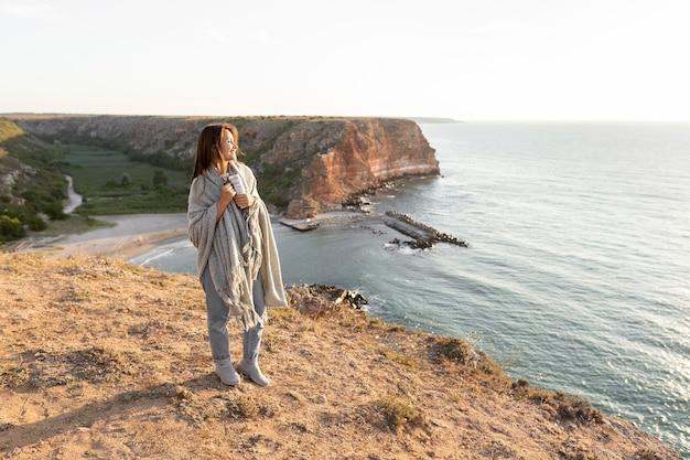Mulher segurando uma garrafa térmica enquanto caminha na costa