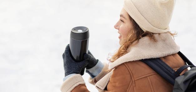 Mulher segurando uma garrafa térmica