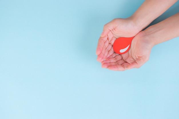 Mulher segurando uma gota de sangue vermelha