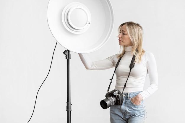 Mulher segurando uma lâmpada de estúdio