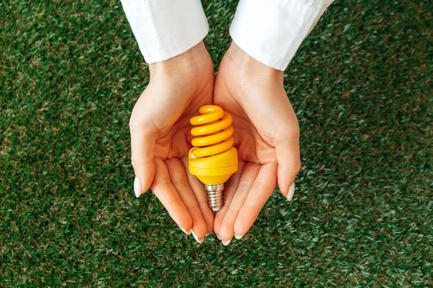 Mulher segurando uma lâmpada nas mãos, acima da grama